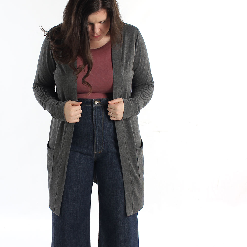 model wears a very long line simple cardigan at mid thigh with patch pockets