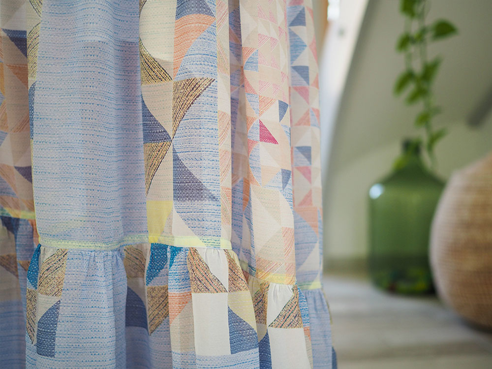 Close up of sheer geometric blue and yellow fabric.