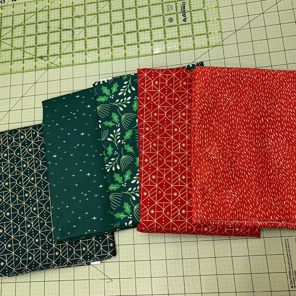 Five Christmas quilting cottons stacked on a cutting table.