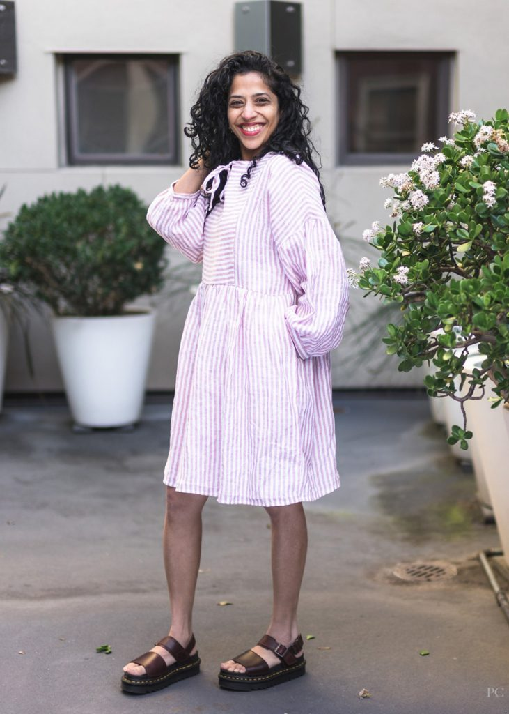 Swetha in her March dress with the neckties tied and her hand in the pockets.