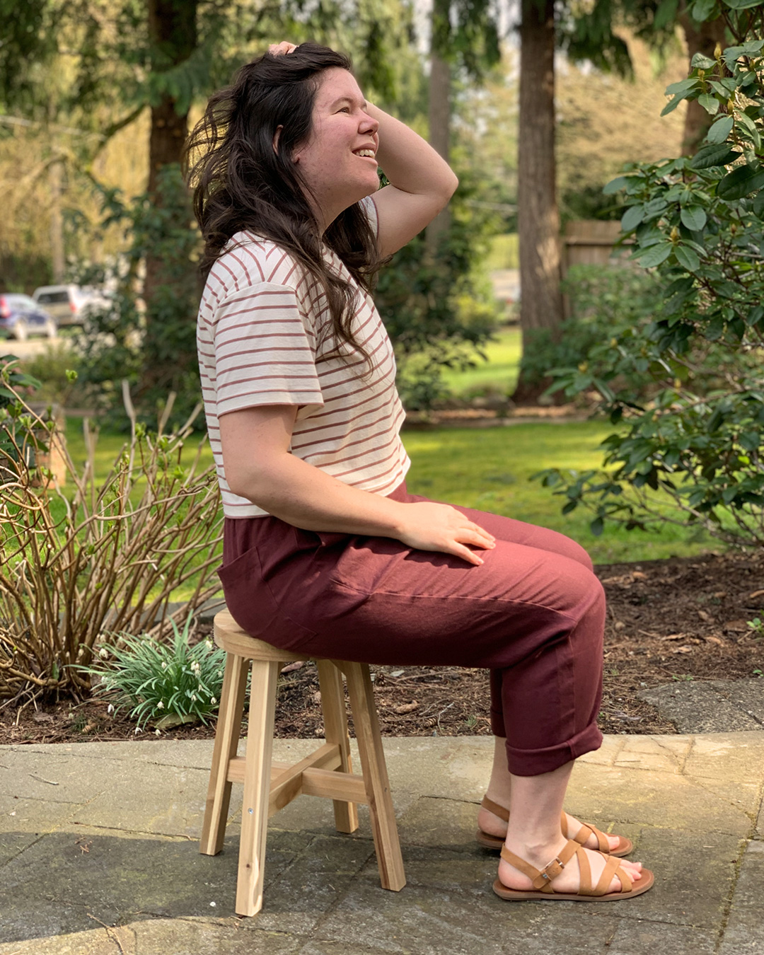 Helen in a cropped Jackson t shirt pattern and linen pair of Arden pants, shown from the side seated.