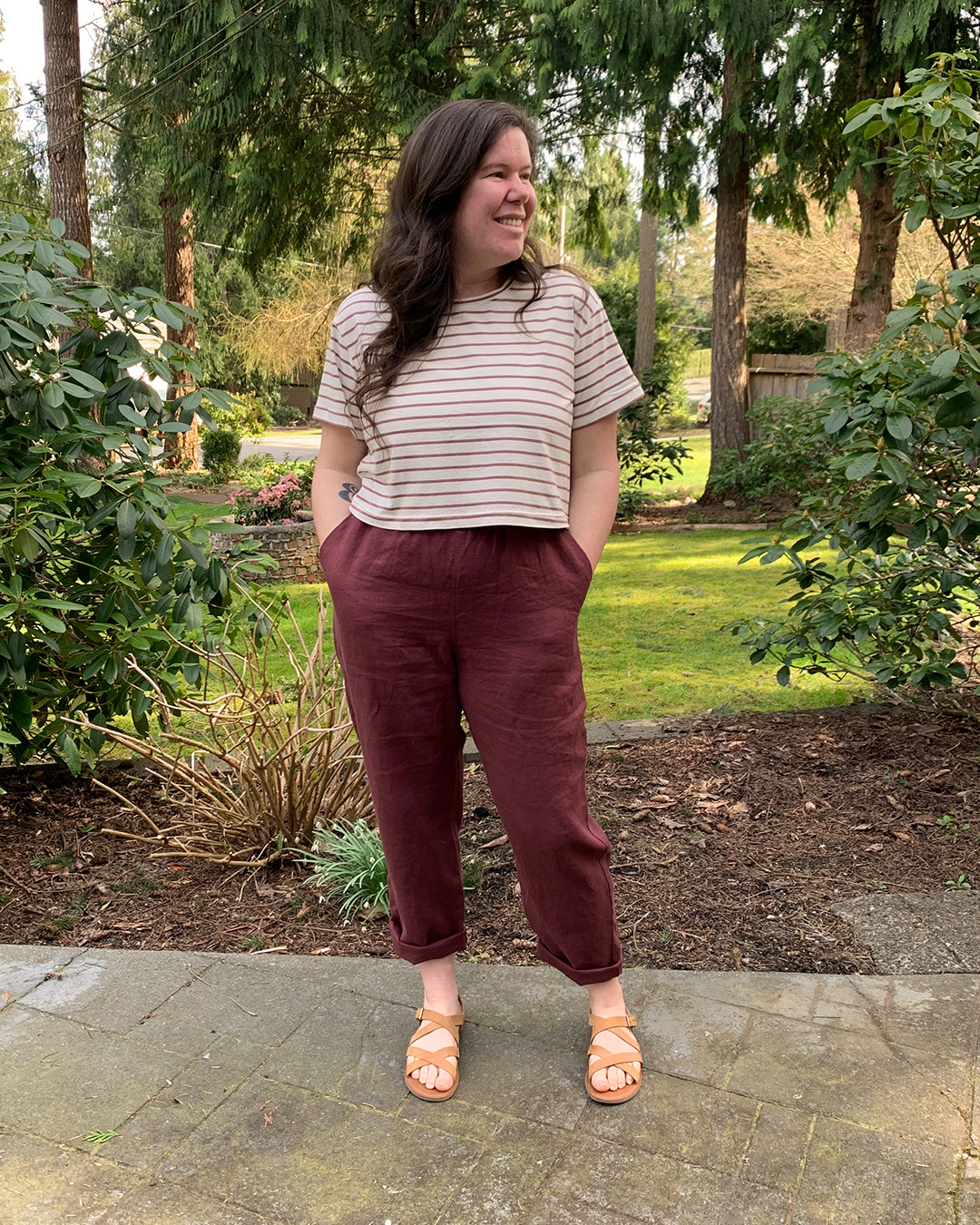 Helen modeling her cropped Jackson Tee paired with burgundy Arden pants, with her hands in her pockets and looking to the side.