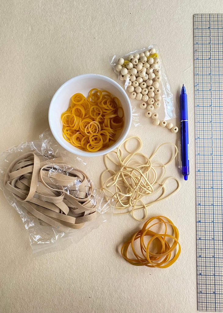 Many tie-dye designs can be created with simple tools like rubber bands and wooden beads.